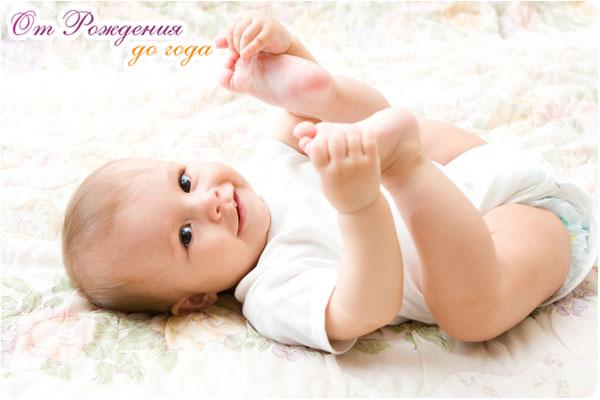 Малыш лежит на спинке и улыбается подняв ножки