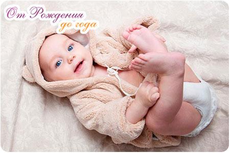 Новорожденный ребенок лежит на спинке и улыбается
