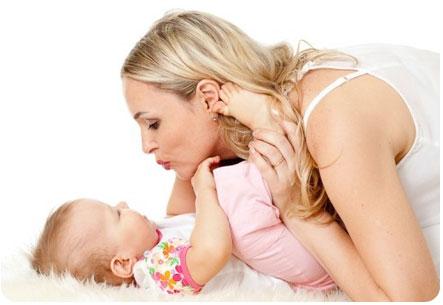 Мама целует свою маленькую дочку