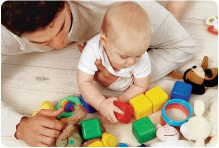 Малыш играет с игрушками совместно с папой