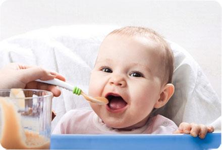 Маленький ребенок с удовольствием ест с ложечки