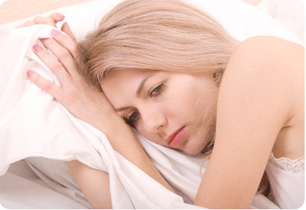 Расстроенная девушка лежит на кровати