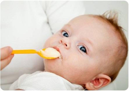 Кормление ребенка с ложечки фруктовым пюре