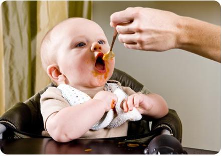 Мама кормит малыша с ложечки. Кроха ест с большим аппетитом