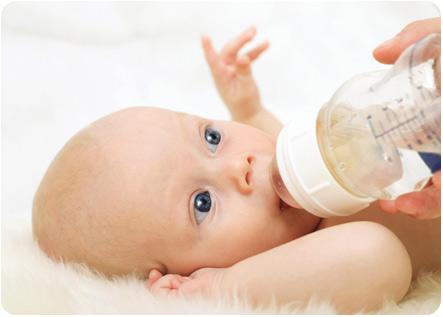 Грудничок пьет воду с бутылочки