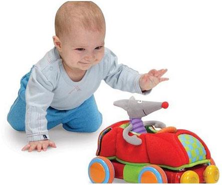 Годовалый ребенок играет с машинкой