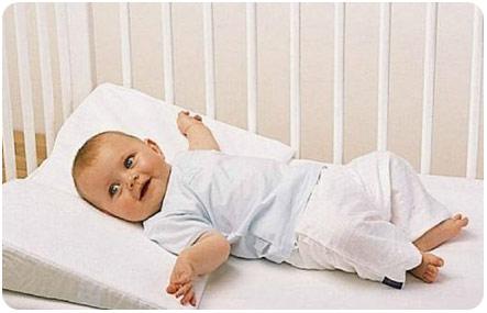 Кроха лежит на подушке в кроватке