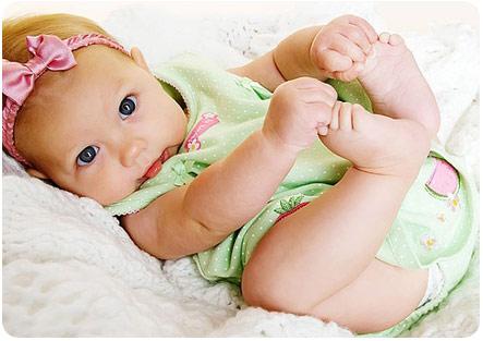 4 месячная малышка лежит на спинке и держится за ножки