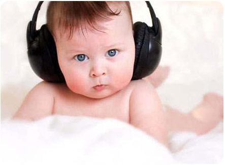Маленький кроха слушает музыку через наушники