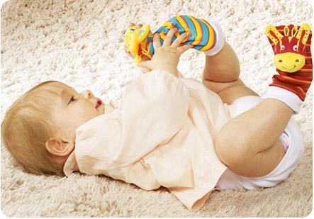 Маленькая кроха играет со своими носочками-игрушками