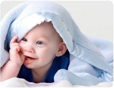 Озорник лежит под одеялом с пальцем во рту