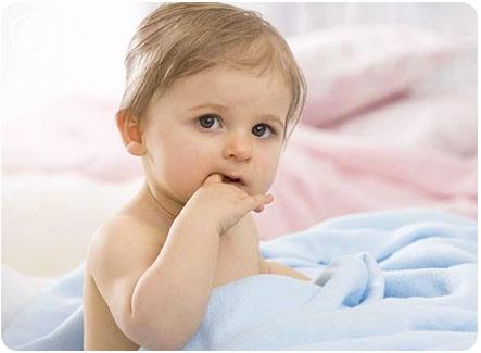 Маленькая кроха сидит в кроватке и сосет свой пальчик