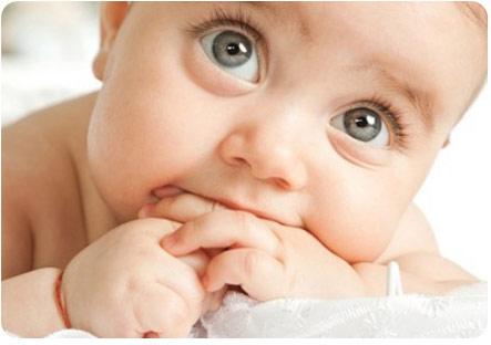 Малыш заинтересованно смотрит и сосет свои пальцы