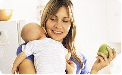 Кормящая мама держит ребенка на руках и ест яблоко