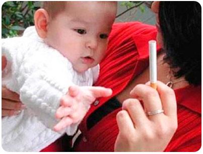 Кроха тянется к сигарете в руках у мамы
