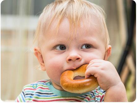 Ребенок пытается жевать бублик