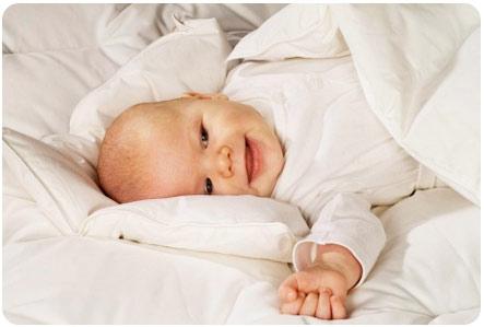 Ребенок лежит в кроватке под одеялом и улыбается