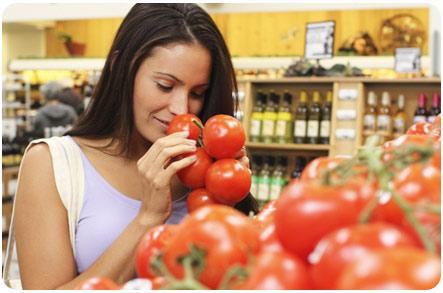 Девушка выбирает в магазине помидоры