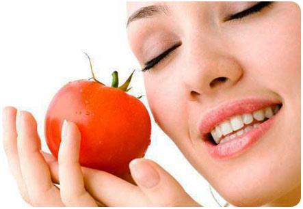 Кормящая мама держит в руках помидор
