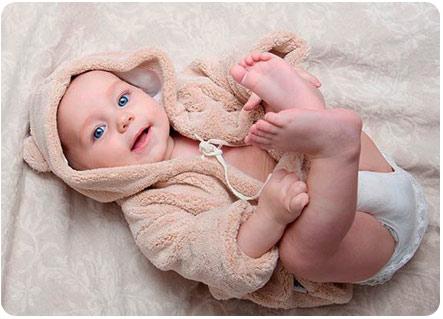 Малыш лежит на спине и улыбается