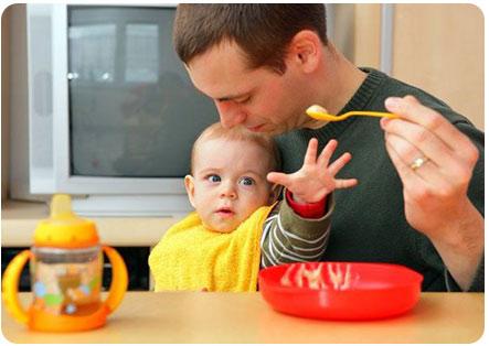 Папа кормит ребенка детской смесью
