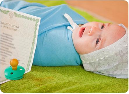 Малыш лежит рядом со свидетельством о рождении