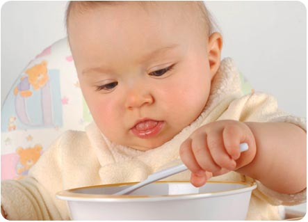 Малыш пытается кушать с ложечки самостоятельно