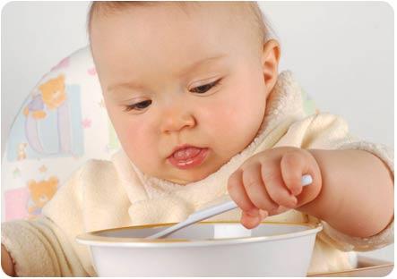 Малыш самостоятельно пытается есть кашу с ложки