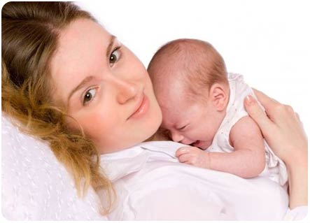 Новорожденный малыш плачет на маминых руках