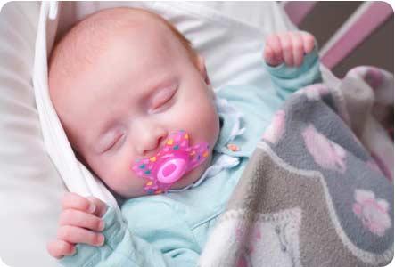 Новорожденный ребенок с соской (пустышкой)