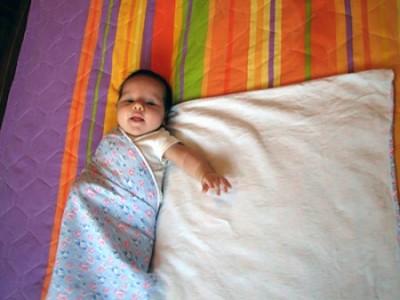 Берем левый верхний угол пеленки и заводим за спину ребенку через его правый бок.
