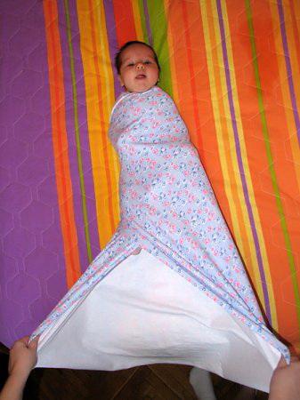 Расправляем нижние углы пеленки, берем их двумя руками.