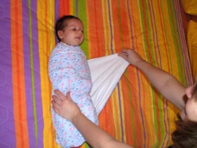 Свободный левый угол проводим через спину и выводим через правое плечо ребенка.