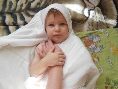 Одной рукой придерживаем пеленку за ушами малыша, второй рукой берем полотно с правой стороны и завидим его за спину через левую подмышку