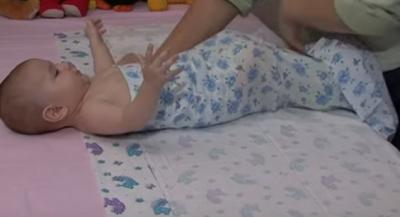 Далее переносим всю левую сторону пеленки малышу под спину