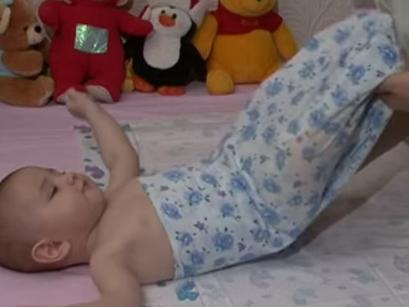 Свободную ткань ниже ножек ребенка подворачиваем ему под колени