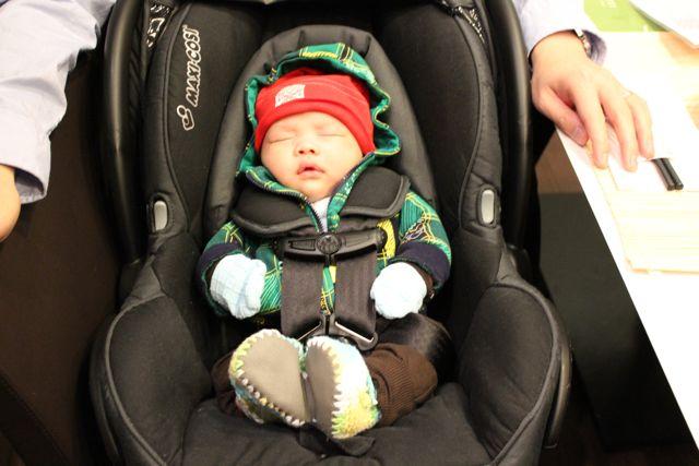 Малыш в оранжевой шапке лежит в автолюльке