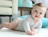 Малыш в полосатом боди на животе, опирается на ручку, на заднем фоне голубая подушка