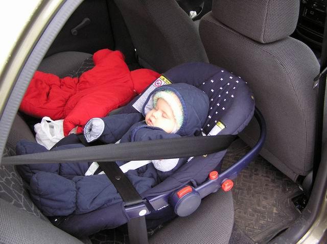 Малыш в синем комбинезоне в автолюльке