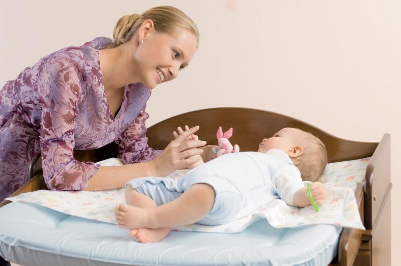 Мама в фиолетовой блузке даёт малышу, лежащему на спине, свой палец