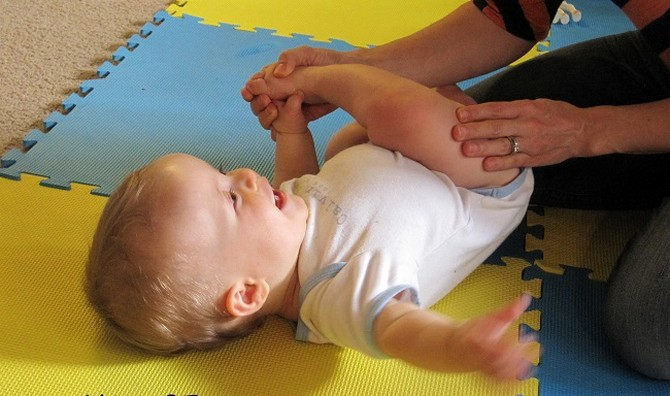 Ножку малыша в белом боди тянут для переворота на жёлто-голубом массажном коврике