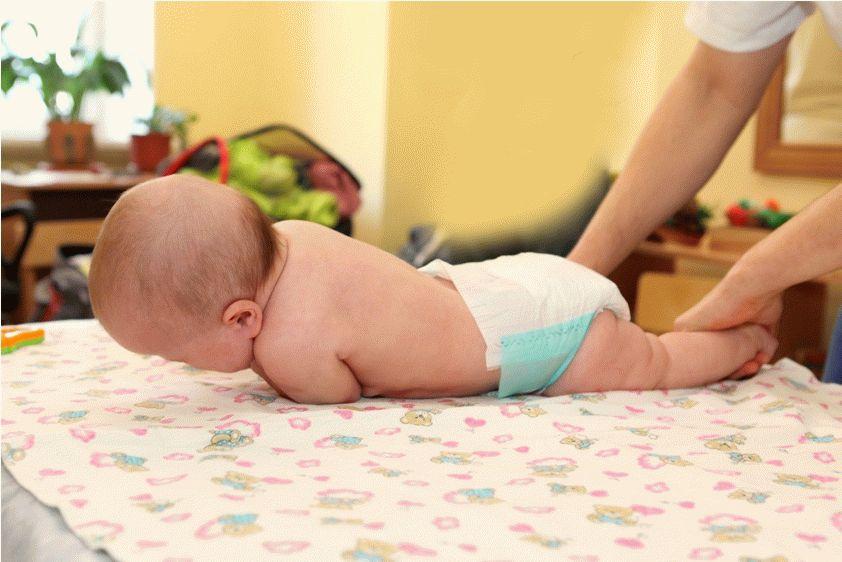 Ребёнка в памперсе перевернули на живот на цветной пелёнке