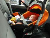 Ребёнок спит в оранжевой автолюльке