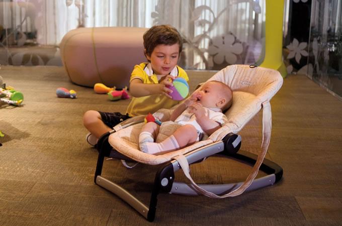 Мальчик держит мячик перед малышом, лежащим в качалке-шезлонге