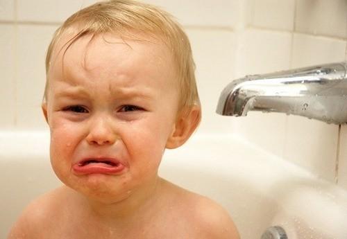Малыш плачет рядом с краном в ванне