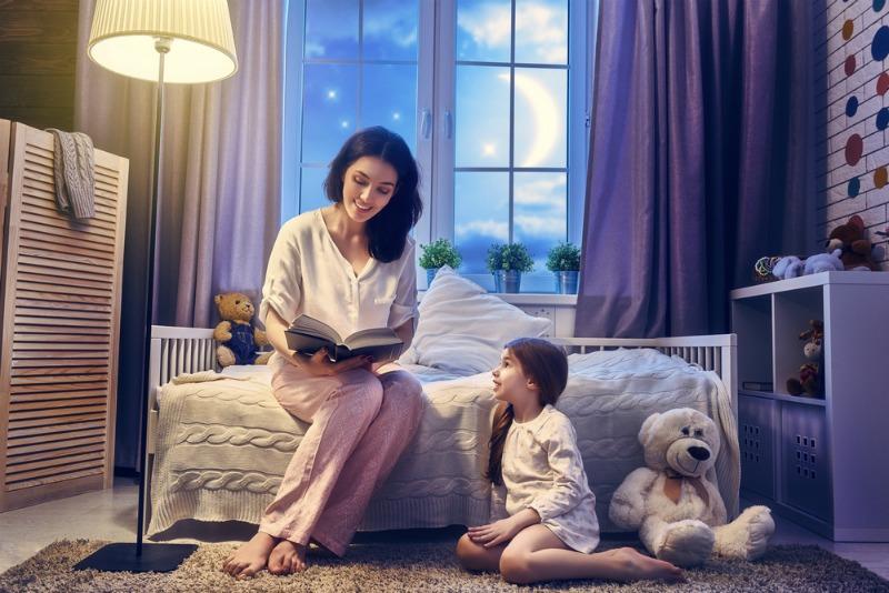 Женщина читает книгу девочке