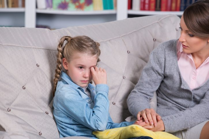 Женщина и плачущая девочка сидят на диване