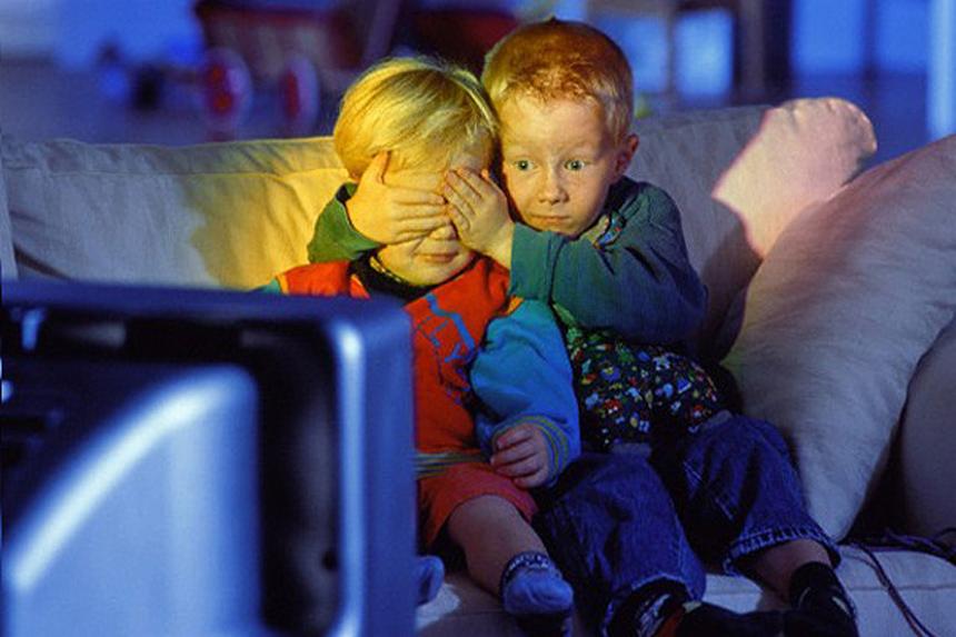 Дети смотрят телевизор в вечернее время