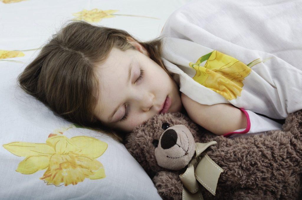 Девочка спит в обнимку с плюшевым мишкой