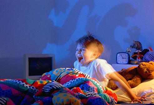 Мальчик кричит, сидя в кровати